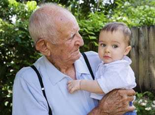 Cute baby boy with great grandfather outdoors.