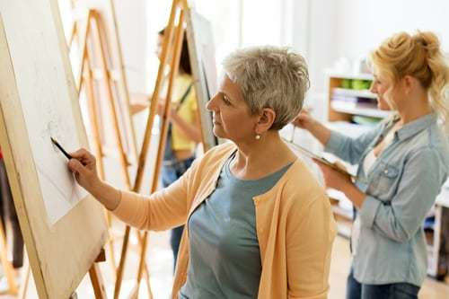 Senior woman drawing on art easel in bright room.