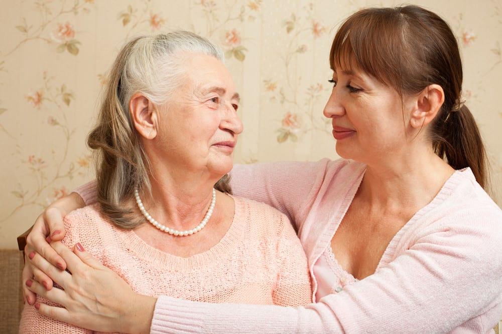 elderly woman and adult daughter embracing, smiling, and looking at each other