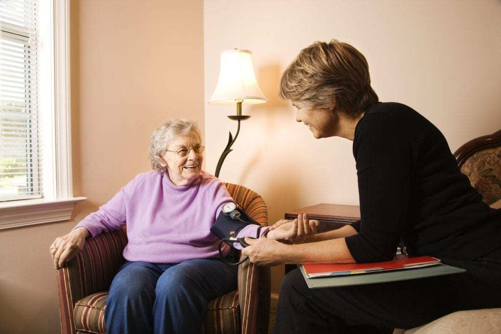 Elderly woman having her blood pressure checked by assisted living staff member in a comfortable living room