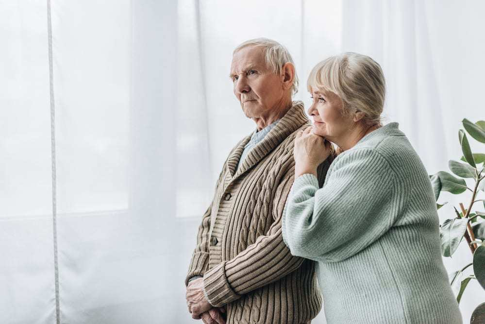 senior couple looking out window, woman's hands resting on man's shoulder