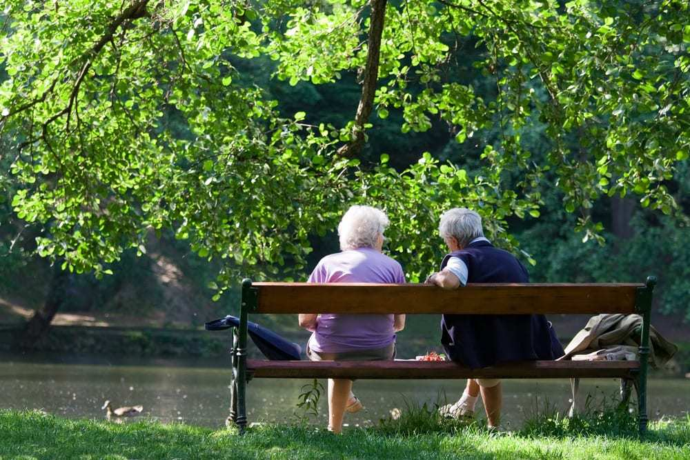 senior man and woman sitting on bench in a park by a lake