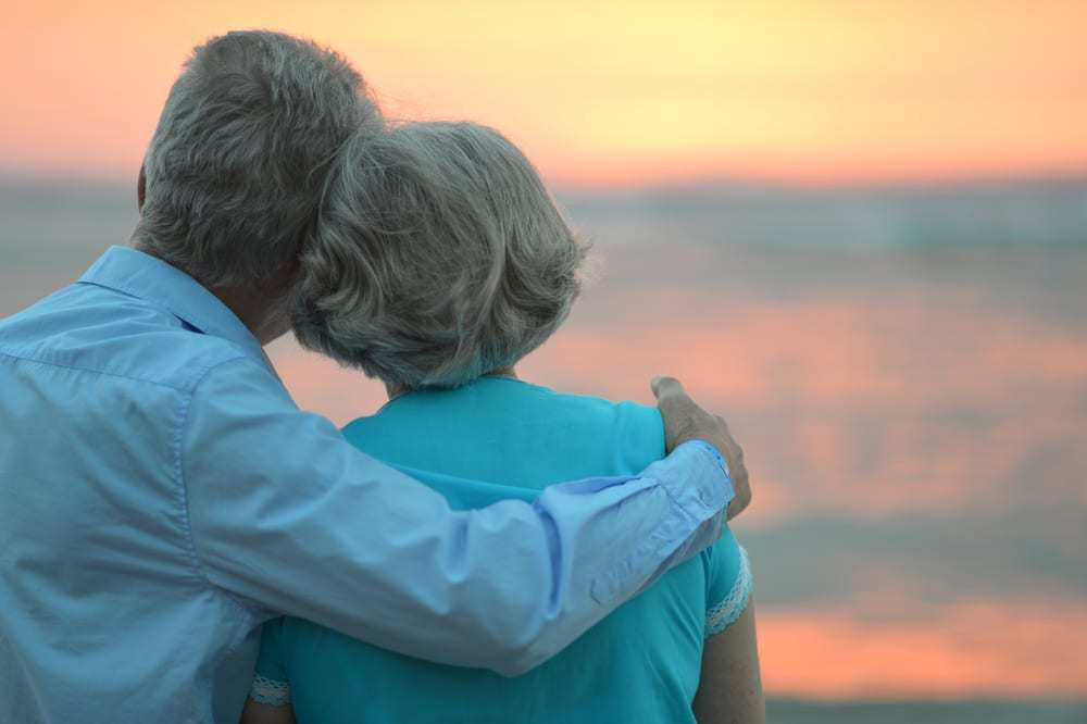 Senior couple embracing at sunset near the sea
