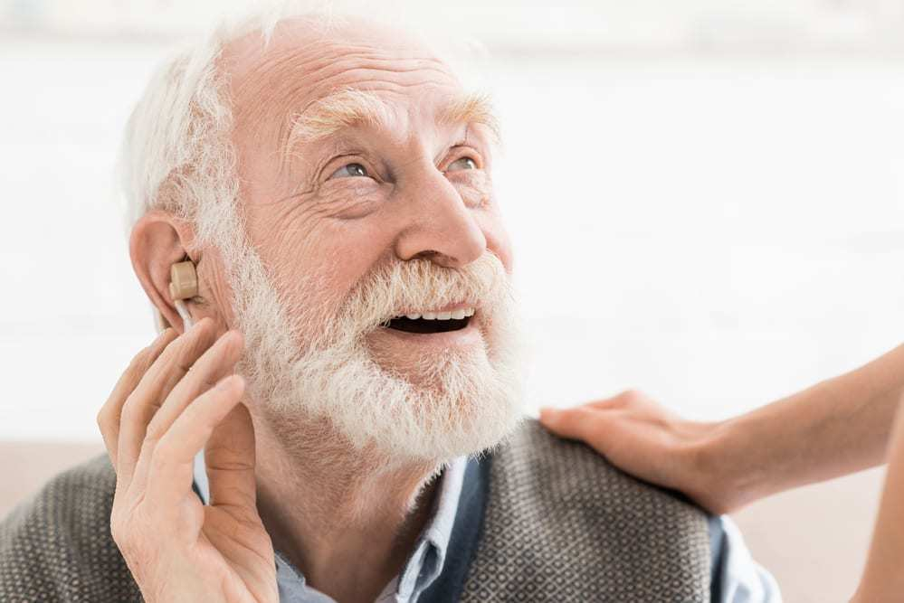 Senior man wearing hearing aid smiling up at someone