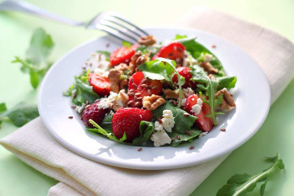 Salad with arugula, goat cheese, strawberries, and walnuts