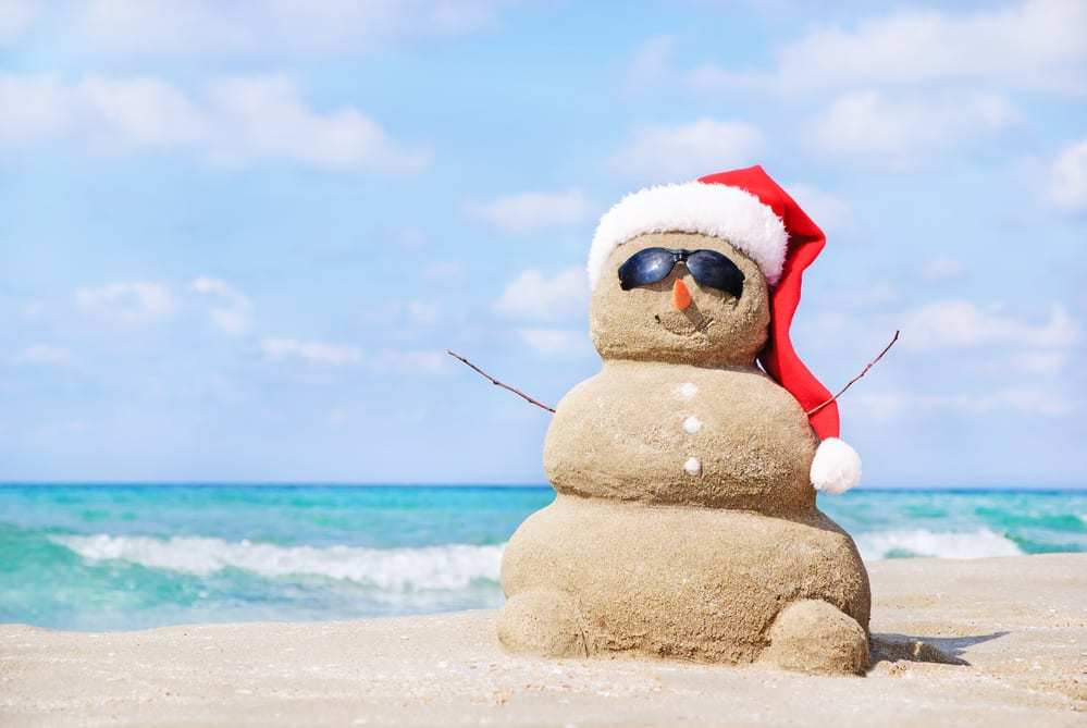 Snowman made of sand wearing sunglasses and santa hat on the beach