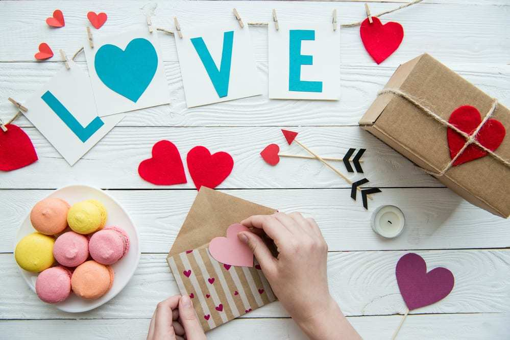 Valentine's day composition with macarons, a gift, letters reading LOVE, paper hearts, etc.