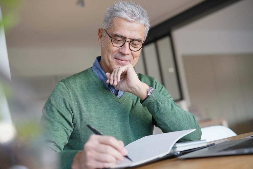 Senior man with small smile writing in journal