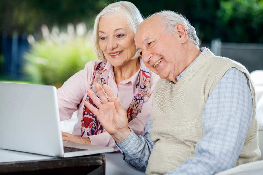 senior couple video chatting on laptop, smiling
