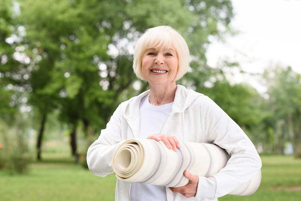 Smiling senior woman in the park holding yoga mat
