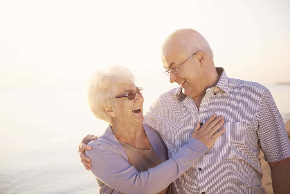 Senior couple smiling and embracing while walking on the beach