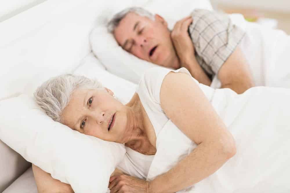 Senior couple in bed, man snoring and woman looking upset