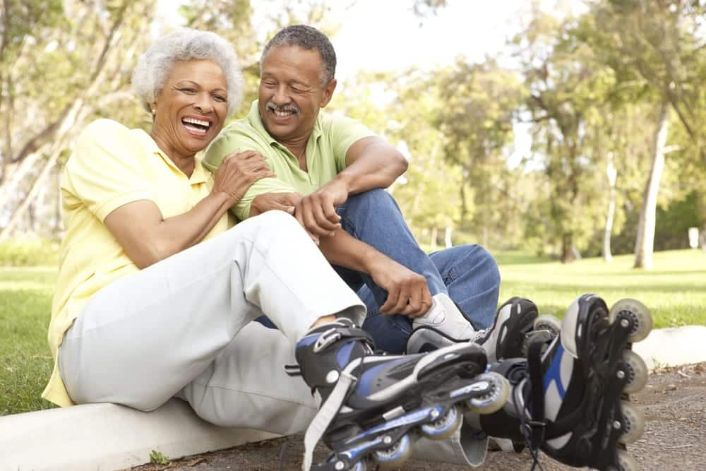 Smiling senior couple wearing roller blades at a park