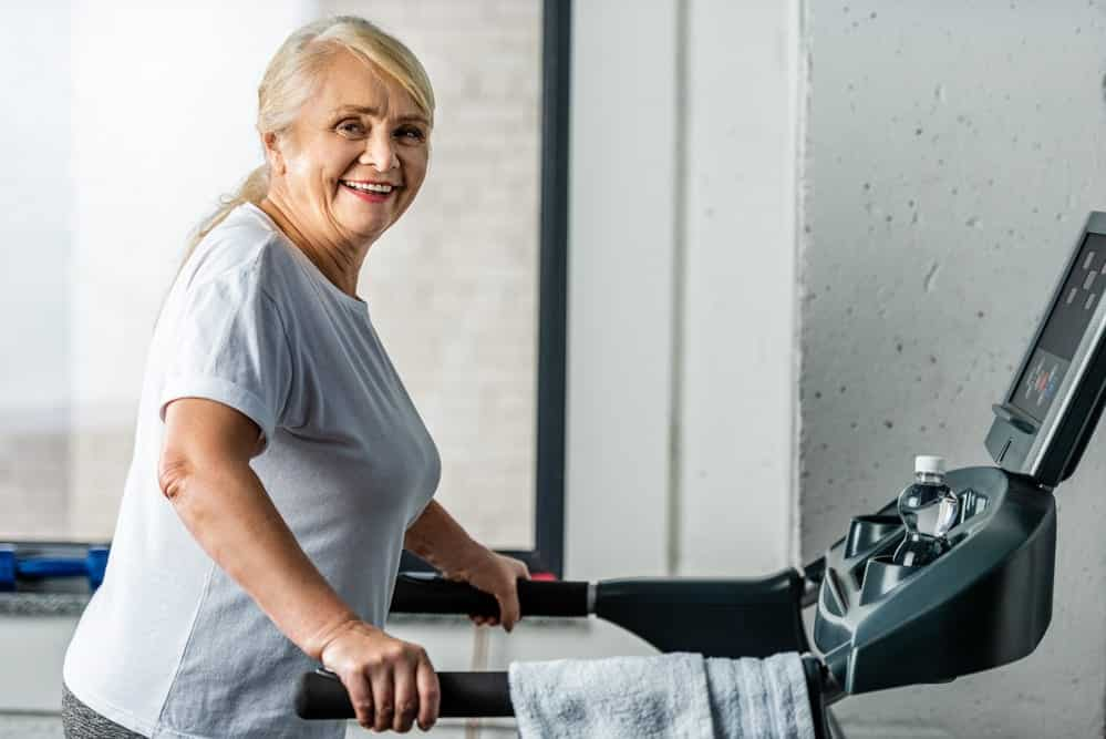Senior woman smiling while walking on treadmill