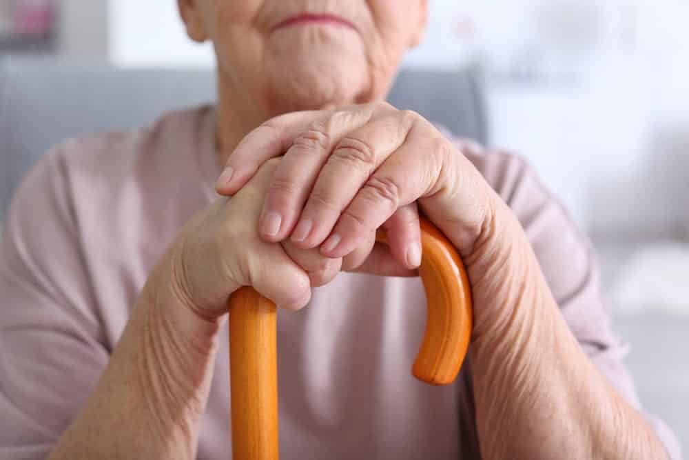 elderly woman leaning on walking stick, close-up