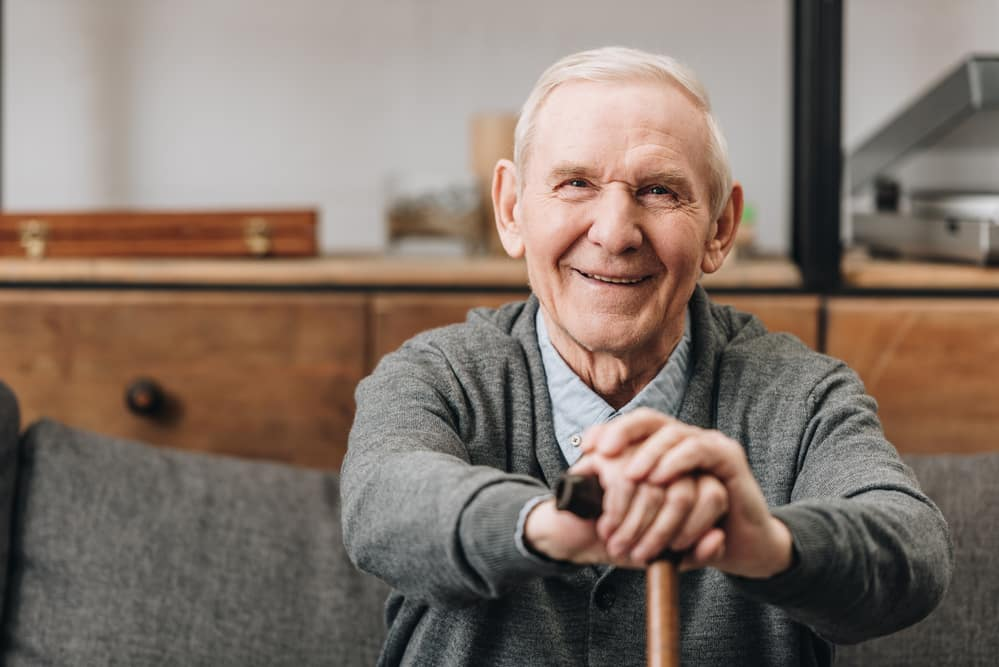Smiling senior man sitting on couch, leaning on cane