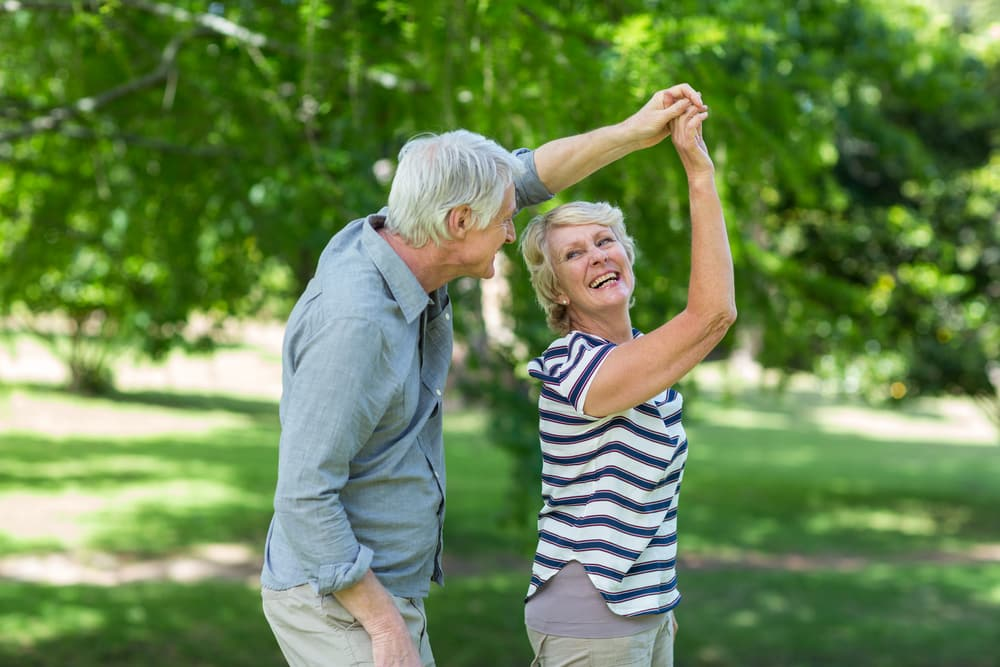 Two seniors dancing together outside, smiling