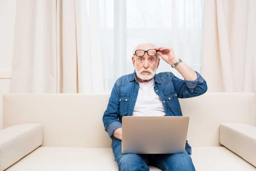 Senior man using laptop on couch, surprised expression