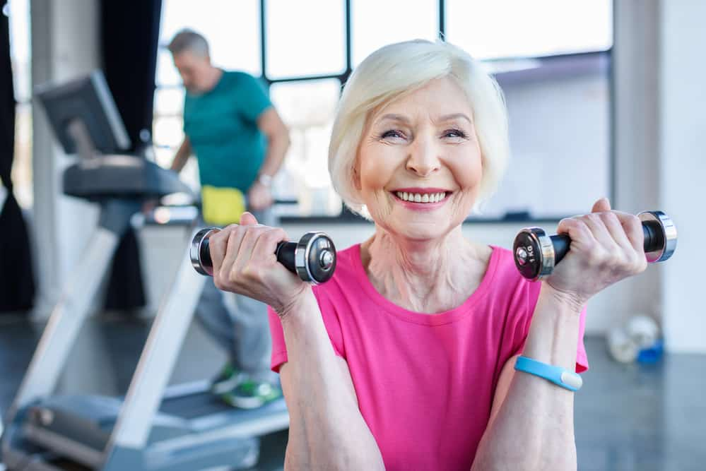 Smiling senior woman holding dumbbells