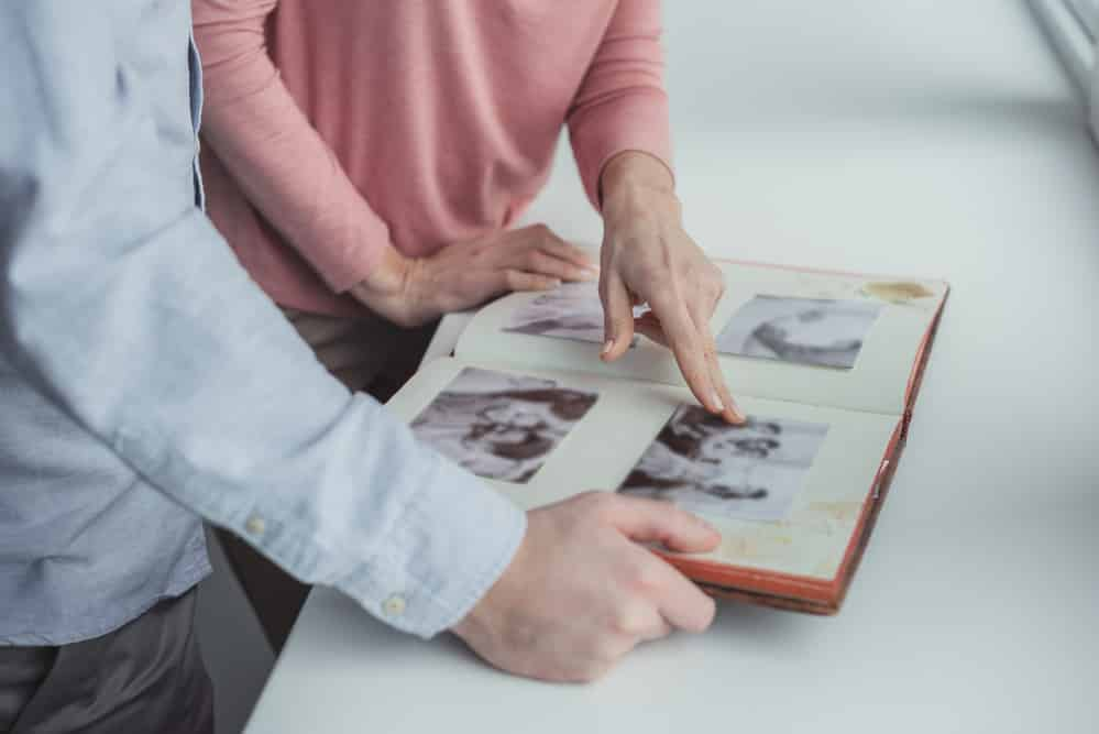 Close-up of man and woman's hands as they look at family photo album