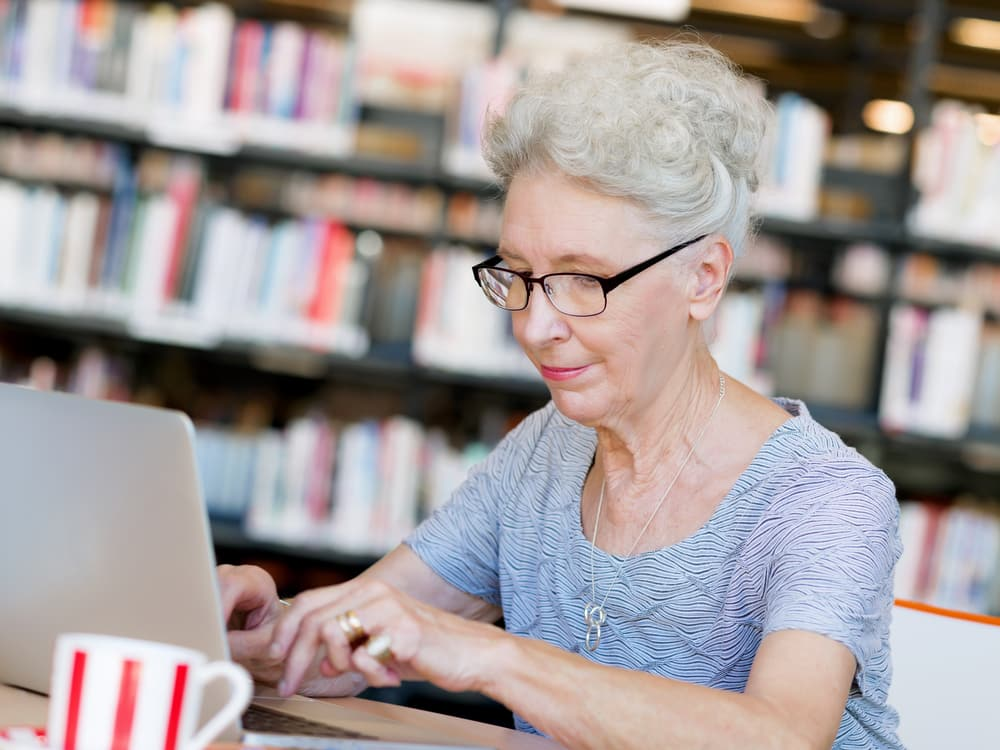 Senior woman working on laptop at library