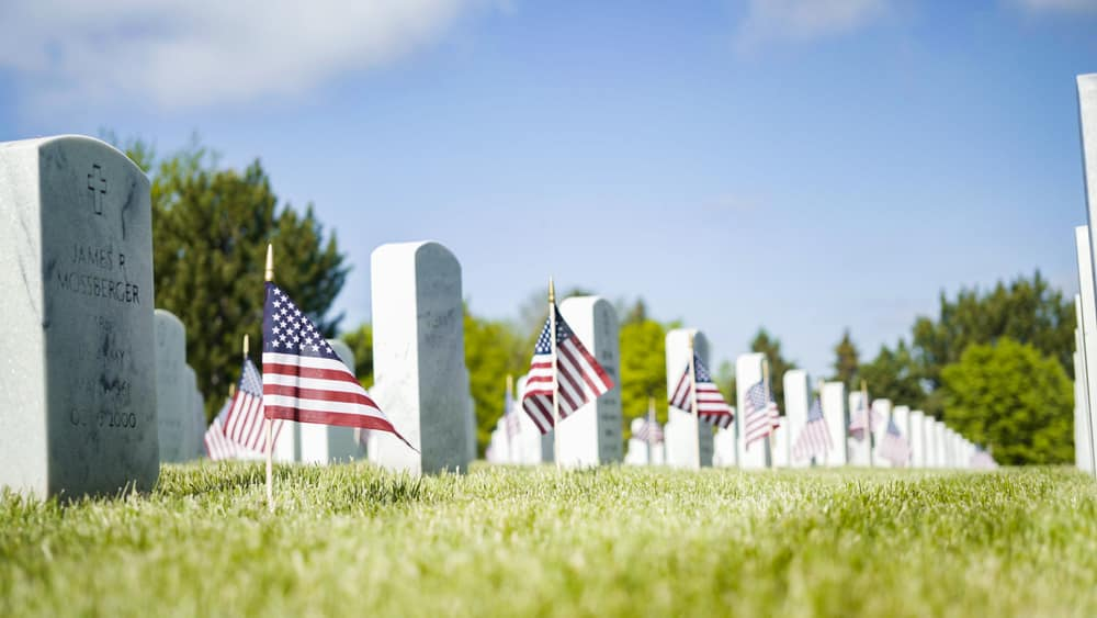 American flags beside gravestones at US National Cemetery
