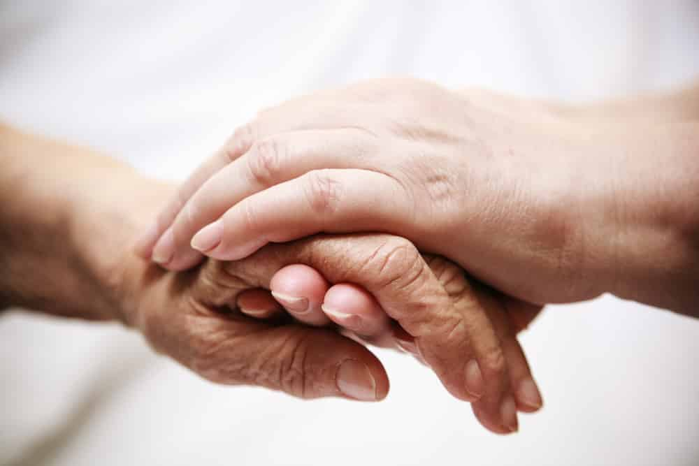 Close-up of young hands comforting old hands